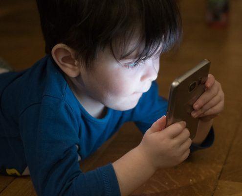 Jongetje kijkt met interesse naar smartphone